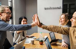 four smiling coworkers group high-fiving over a conference desk